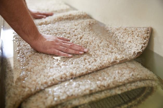 Tapete sujo imersão em solução química especial em serviço de limpeza de carpete
