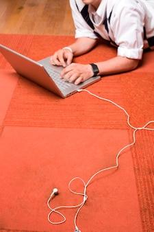 Tapete vermelho, laptop, fones de ouvido brancos