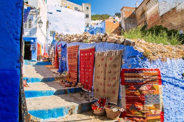 Tapetes tradicionais na rua azul chefchaouen.