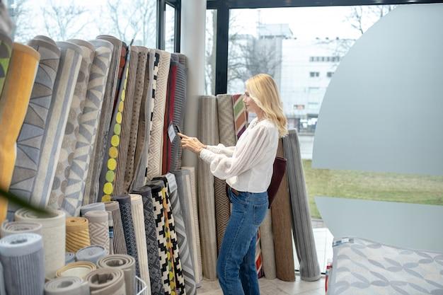 Tapetes, uma escolha. mulher com cabelo até os ombros com um smartphone em pé na frente dos tapetes e tirar uma foto no salão de móveis.