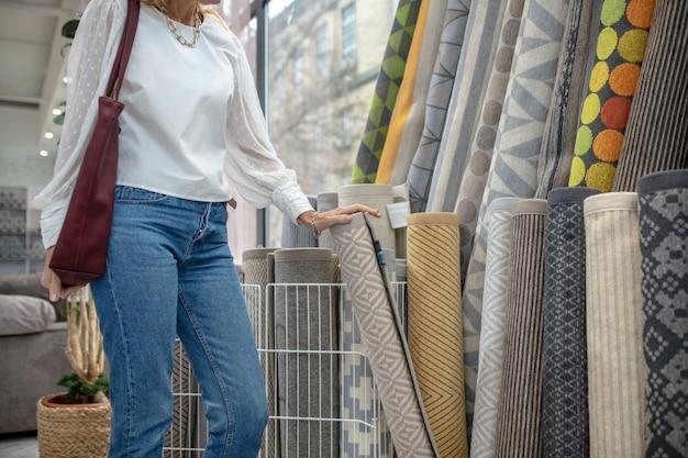 Tapetes, variedade. mulher de blusa branca e calça jeans em pé no departamento de carpetes de uma loja de móveis, segurando um tapete com a mão, o rosto não é visível.