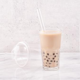 Tapioca pérola bola bolha leite chá, bebida popular de taiwan, em copo com canudo na mesa de mármore branco e bandeja de madeira, close-up, copie o espaço