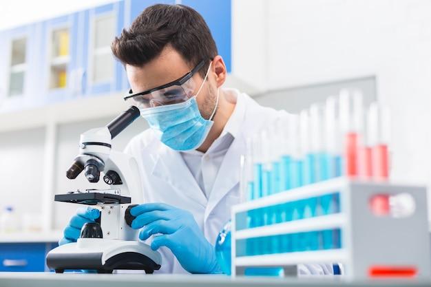 Tarefa difícil. assistente de laboratório masculino muito habilidoso usando máscara enquanto toca o microscópio e conduz pesquisas