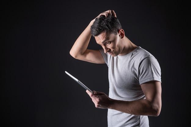 Tarefa difícil. bom homem inteligente e confuso olhando para a tela do tablet e tocando seu cabelo enquanto resolve uma tarefa difícil