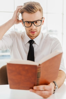 Tarefa difícil do chefe. jovem bonito em trajes formais segurando um livro e lendo enquanto está sentado no escritório