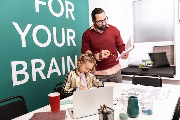 Tarefa em casa. professor adulto, de cabelos escuros e barbudo, usando óculos, dando uma tarefa em casa para seu aluno