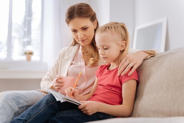 Tarefa escolar. linda garota séria e inteligente sentada junto com a mãe e escrevendo em seu caderno enquanto faz uma tarefa em casa
