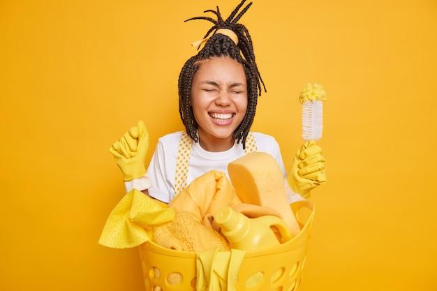 Tarefas domésticas diárias. a dona de casa radiante com dreadlocks fecha o punho fica muito feliz perto do cesto de roupa suja segura a escova vestida casualmente e expressa emoções positivas isoladas sobre um fundo amarelo