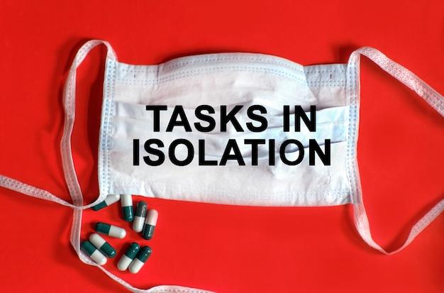 Tarefas em isolamento - texto em uma máscara protetora, comprimidos em um fundo vermelho
