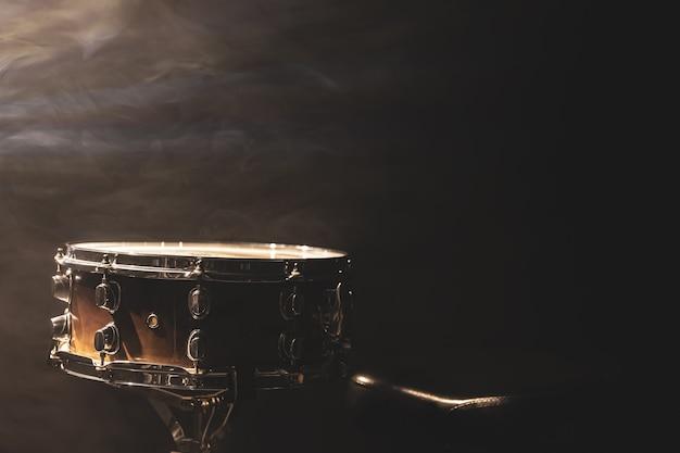 Tarola em fundo preto, instrumento de percussão no escuro com fumaça de palco, copie o espaço.