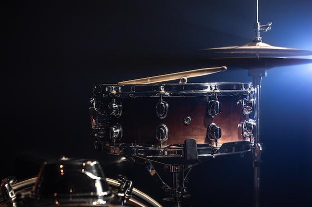 Tarola, instrumento de percussão em um fundo escuro com iluminação de palco.