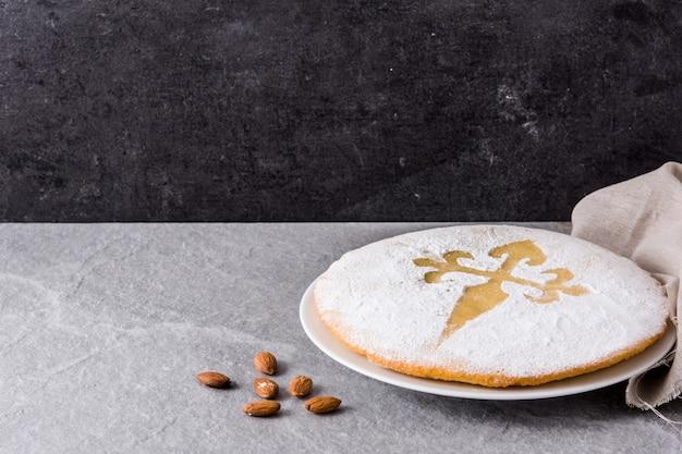 Tarta de santiago. bolo de amêndoa tradicional de santiago na espanha em fundo cinza