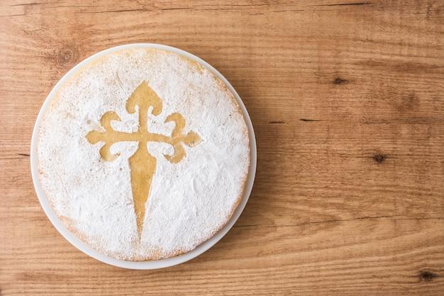 Tarta de santiago. bolo de amêndoa tradicional de santiago na espanha na mesa de madeira
