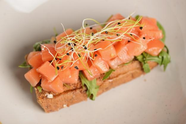 Tartare de salmão com rúcula em um pedaço de pão. em um prato branco