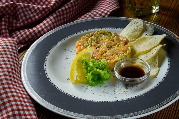 Tartare de salmão fresco, abacate com pão torrado e molho de soja na chapa branca sobre fundo de madeira em composição com pano vermelho.