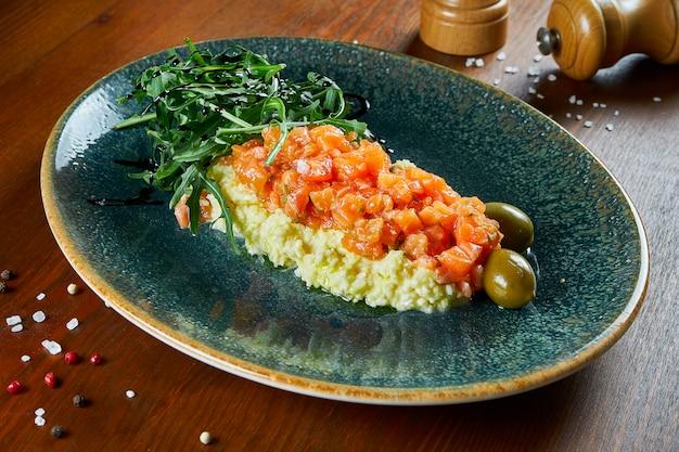 Tartare de salmão salgado em uma almofada de ovos mexidos com azeitonas e rúcula em um prato azul em uma mesa de madeira. antipasti. delicioso e saudável café da manhã. fechar-se