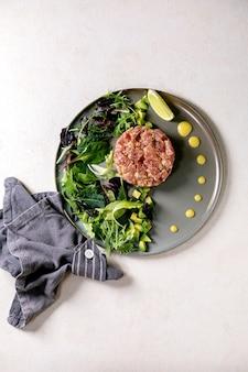 Tártaro de atum com salada verde, limão, abacate e molho de mostarda servindo em prato de cerâmica sobre mesa de textura branca. postura plana, copie o espaço. jantar fino, aperitivo de restaurante