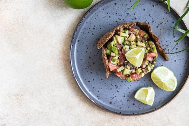 Tártaro de atum e abacate cru servido com biscoitos de pão de centeio e tártaro de peixe de limão gourmet