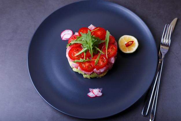 Tártaro de atum fresco com abacate, rúcula, tomate cereja, rabanete, pimenta e limão. aperitivo frio tradicional da culinária francesa. close-up, foco seletivo, vista superior.
