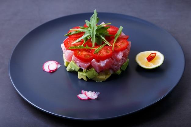 Tártaro de atum fresco com abacate, rúcula, tomate cereja, rabanete, pimenta e limão. aperitivo frio tradicional da culinária francesa. close-up, foco seletivo.
