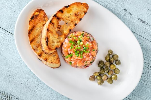 Tártaro de salmão com ciabatta torrado e alcaparras