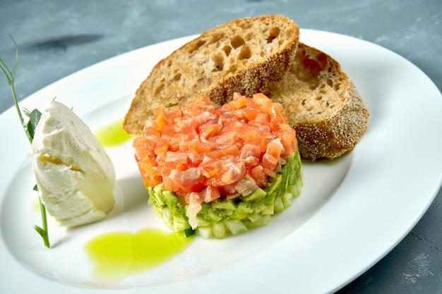 Tártaro de salmão e abacate, croutons em um prato branco no concreto