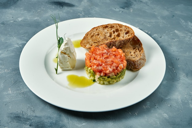 Tártaro de salmão e abacate, croutons em um prato branco sobre uma superfície cinza.