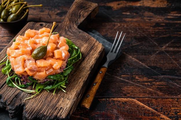 Tártaro de salmão ou tártaro com cebola roxa, abacate, rúcula e alcaparras. fundo de madeira escuro. vista do topo. copie o espaço.