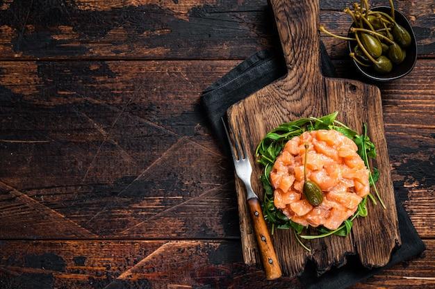 Tártaro de salmão ou tártaro com cebola roxa, abacate, rúcula e alcaparras. mesa de madeira escura. vista do topo.