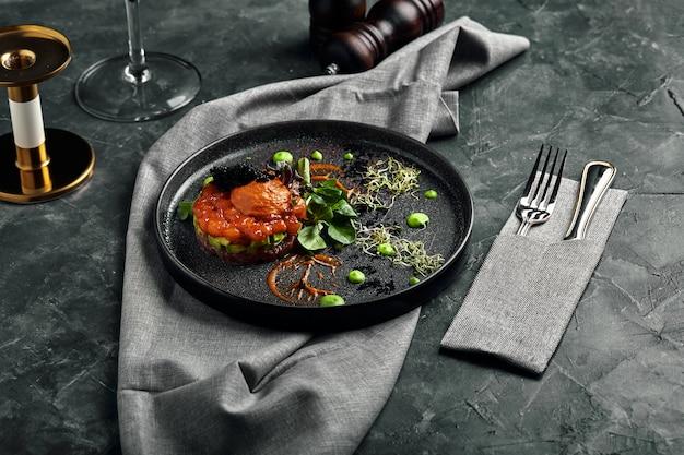 Tártaro fresco com caviar de salmão, abacate e vermelho num prato