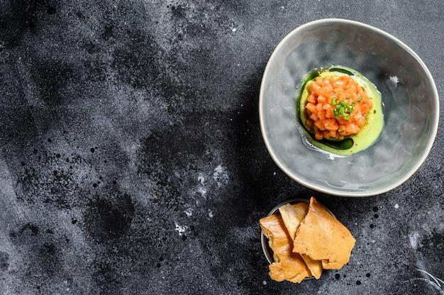 Tártaro fresco com salmão, abacate. fundo preto. vista do topo. copie o espaço