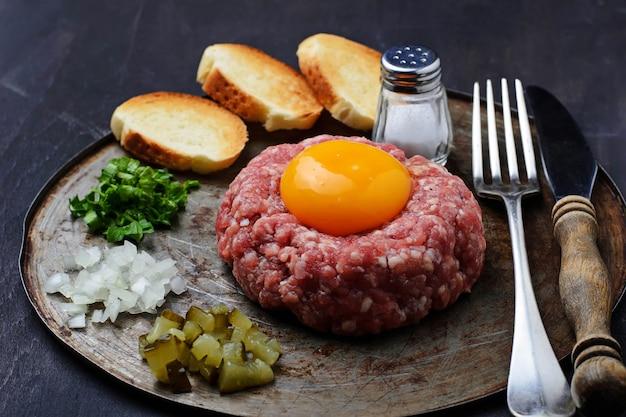 Tártaro fresco da carne com ovo, o pepino conservado e a cebola.