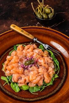 Tártaro ou tártaro com salmão, cebola roxa, rúcula e alcaparras em prato rústico. fundo escuro. vista do topo.