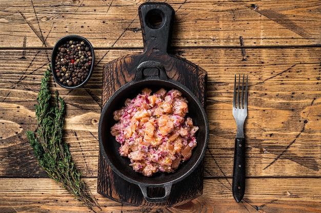 Tártaro ou tártaro com salmão, cebola roxa, rúcula e alcaparras em uma panela