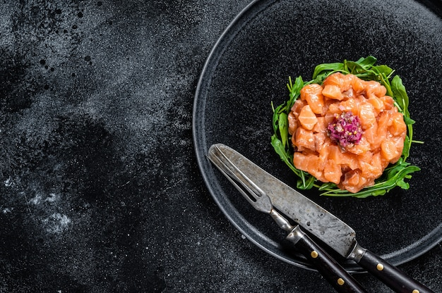 Tártaro ou tártaro de salmão cru com cebola roxa, rúcula e alcaparras em chapa preta. fundo preto. vista do topo. copie o espaço.