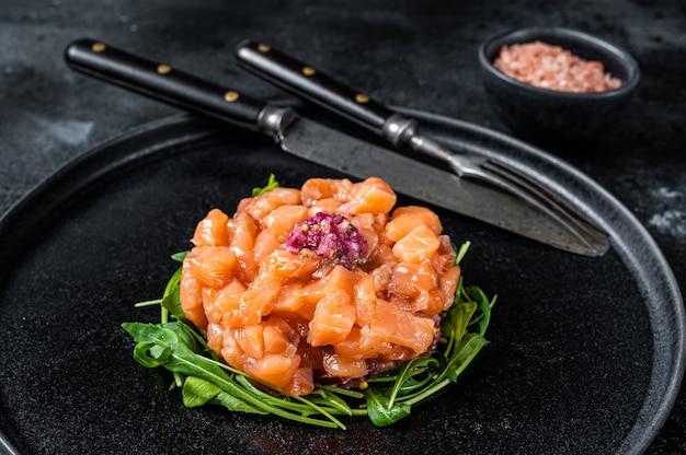 Tártaro ou tártaro de salmão cru com cebola roxa, rúcula e alcaparras em chapa preta. fundo preto. vista do topo.