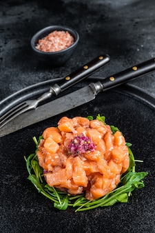 Tártaro ou tártaro de salmão cru com cebola roxa, rúcula e alcaparras em chapa preta. mesa preta. vista do topo.