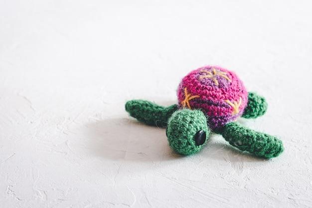 Tartaruga de crochê feito à mão em um fundo branco.