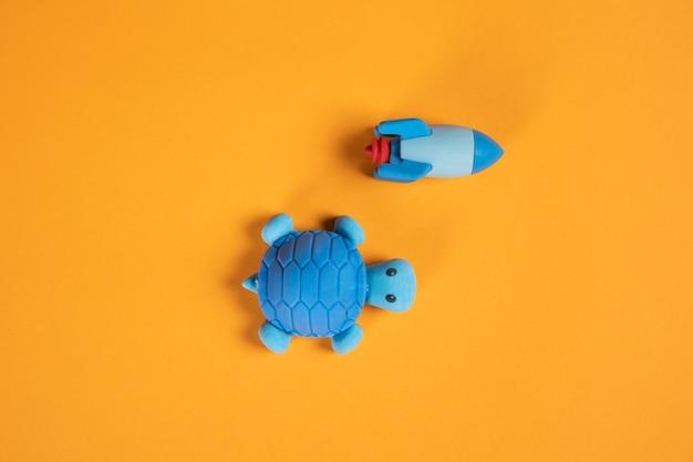 Tartaruga e foguete competem em fundo laranja