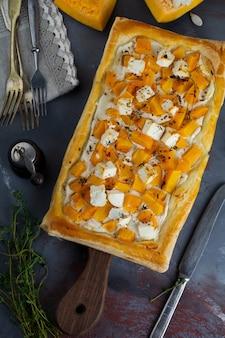 Tarte com abóbora, queijo feta, ricota e tomilho em uma superfície de concreto escura