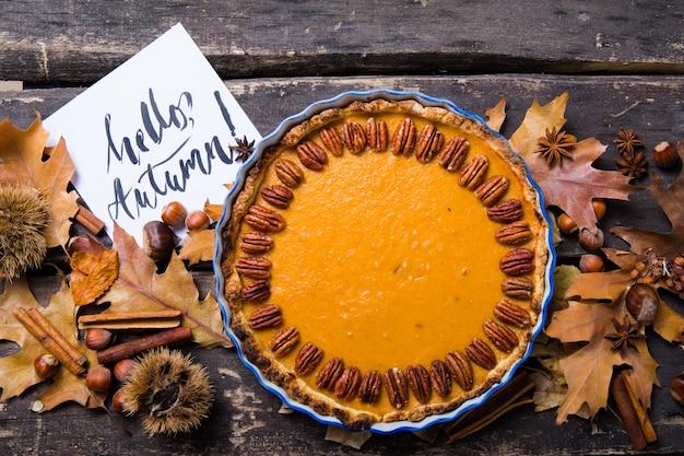 Tarte de abóbora com porca de noz-pecã e canela no fundo rústico, vista superior, espaço da cópia. pastelaria caseira de outono para o dia de ação de graças