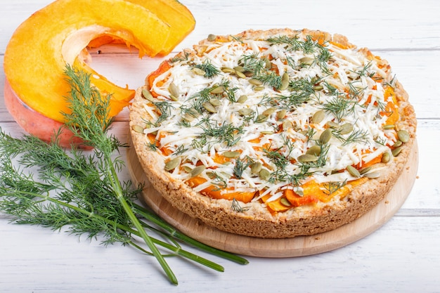 Tarte de abóbora doce com queijo e aneto em de madeira branco.