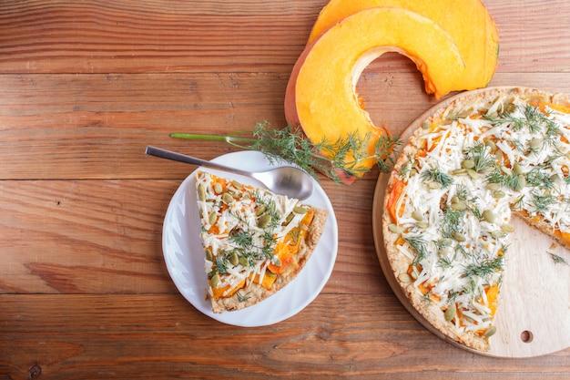 Tarte de abóbora doce com queijo e aneto no fundo de madeira marrom.