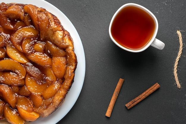 Tarte tatin com pêssegos e caramelo em um prato branco sobre um fundo escuro ao lado da xícara branca