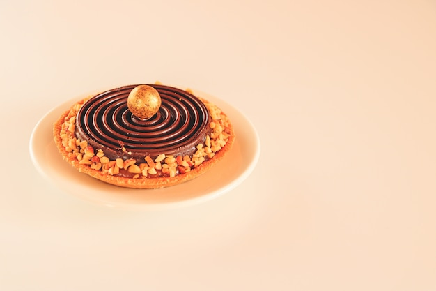 Tartlet com caramelo coberto com chocolate e decorado com chips de nozes.