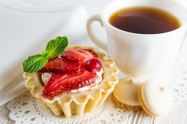 Tartlet com morangos frescos e cream cheese, uma xícara de chá e biscoitos pequenos.