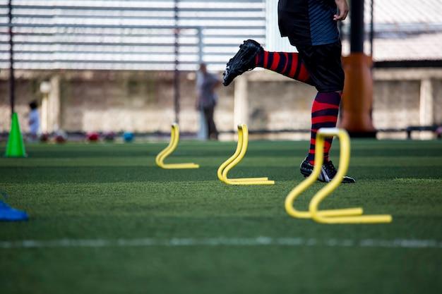 Táticas de bola de futebol em campo de grama com barreira para treinar habilidades de salto de crianças na academia de futebol