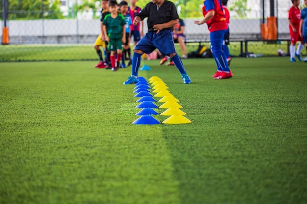 Táticas de bola de futebol no campo de grama com cone de barreira para treinar a habilidade de salto de crianças na academia de futebol