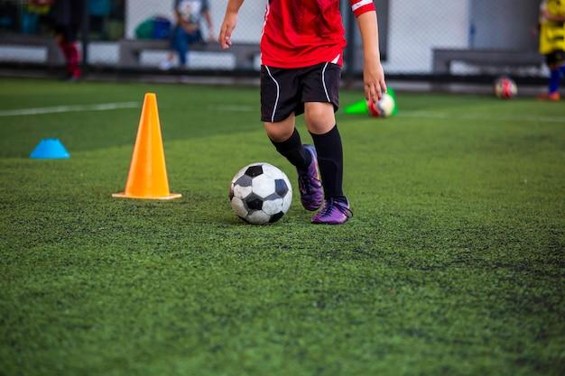 Táticas de bola de futebol no campo de grama com cone para o treinamento de crianças em segundo plano na academia de futebol