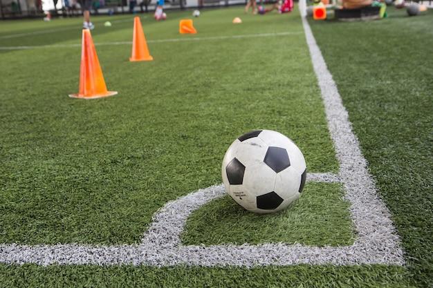 Táticas de bola de futebol no campo de grama com cone para treinamento